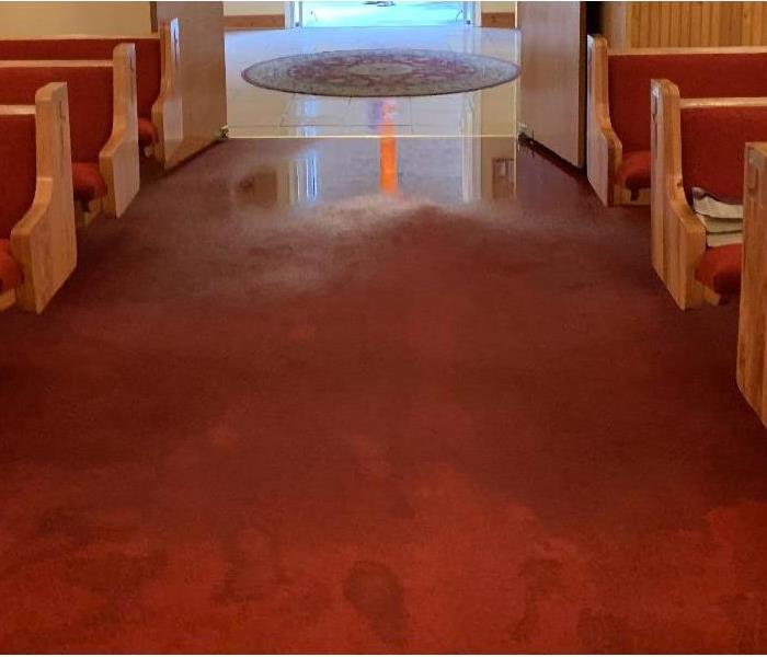 Carpet and floor in entry of church is flooded with water.