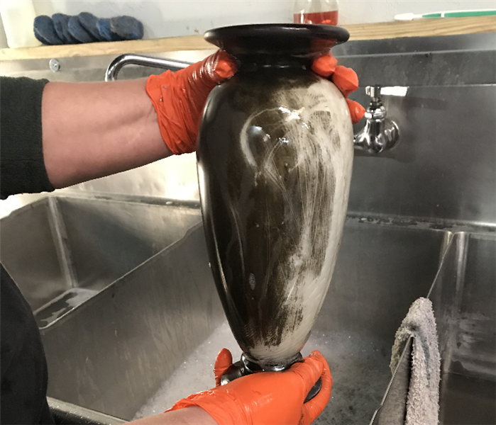 SERVPRO technician holding soot covered vase over sink with orange gloves.