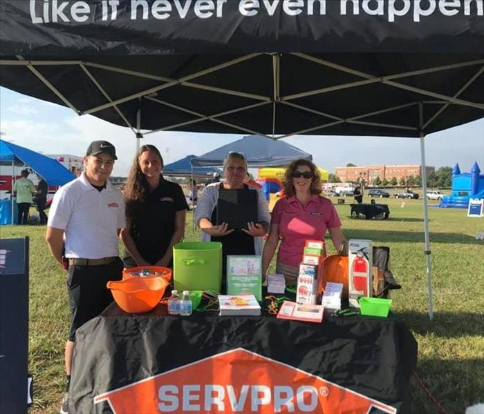 4 SERVPRO team members standing behind table with promotional items under branded tent