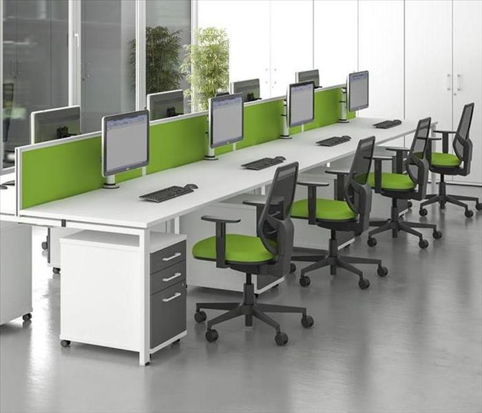 Green and white office space with multiple work stations